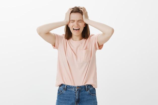 苦しんで動揺している泣いている女性はすべてを失い、否定的に頭を振って、ストレスを感じているように見えます