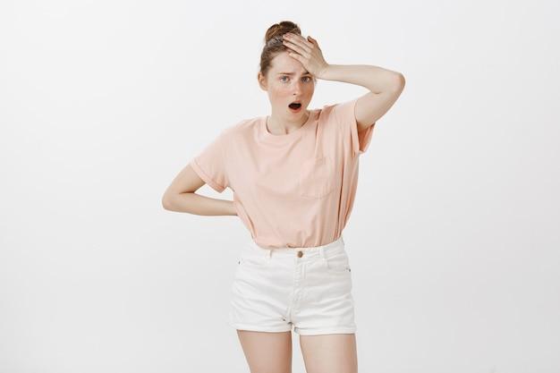 Обеспокоенная и обеспокоенная девочка-подросток позирует у белой стены