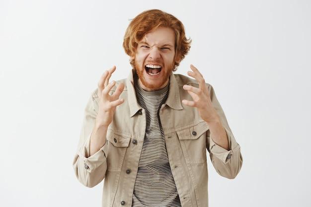 Ragazzo rosso barbuto angosciato e arrabbiato in posa contro il muro bianco