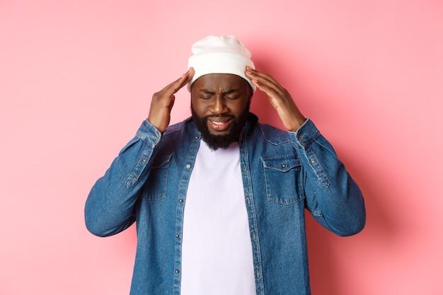 Uomo nero in difficoltà che ha mal di testa, tocca la testa e fa una smorfia con il viso preoccupato, in piedi su sfondo rosa