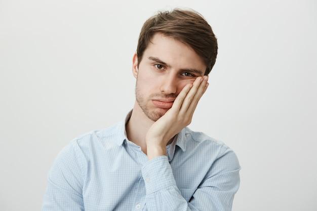 Uomo annoiato angosciato si appoggia al palmo, con aria riluttante