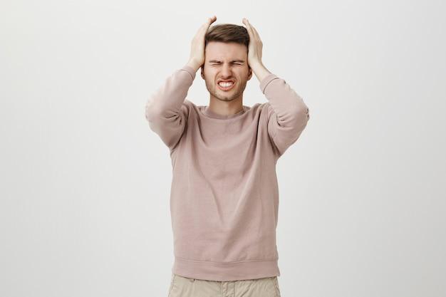 苦しんでいる絶望的な男は後悔を表明し、失望した頭に手をつないで