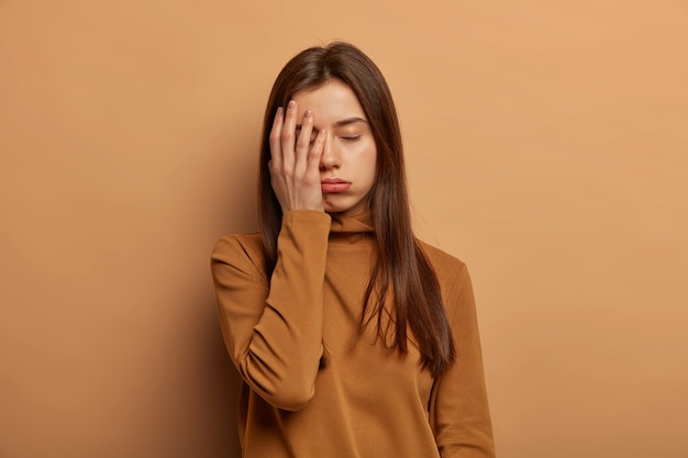 피곤한 여성은 손바닥으로 얼굴을 가리고, 지루하고 피곤하며, 밤새도록 시험 준비를 마치고 잠을 원하고, 휴식이나 지원이 필요합니다.