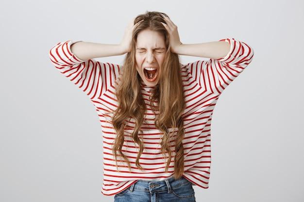 Обеспокоенная девушка кричит и отрицательно качает головой, выглядит подавленной