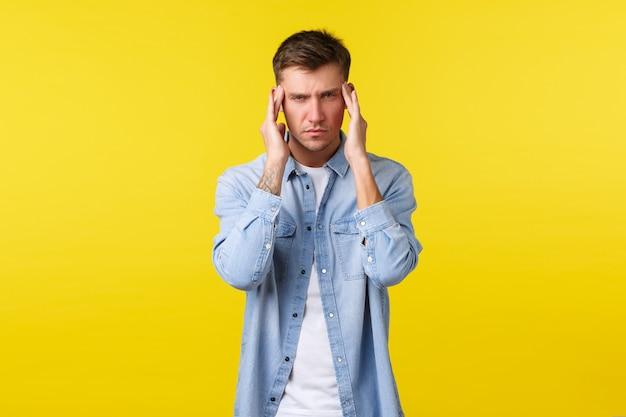 Uomo biondo bello afflitto che sente stress e affaticamento. ragazzo che soffre di mal di testa, tocca il dolore e fa una smorfia di dolore. uomo con tempie di sfregamento di emicrania, cercando di messa a fuoco, sfondo giallo.