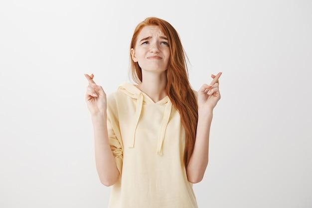 神を懇願するような苦しめられた希望に満ちた赤毛の女性、クロスフィンガー幸運と必死に見上げる