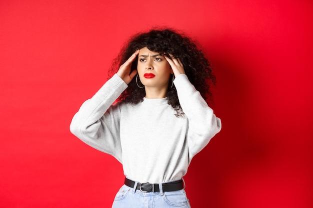 Проблемная итальянская девушка с вьющимися волосами, касаясь головных висков и плохое самочувствие, с головной болью, глядя в сторону, стоя на красном фоне.