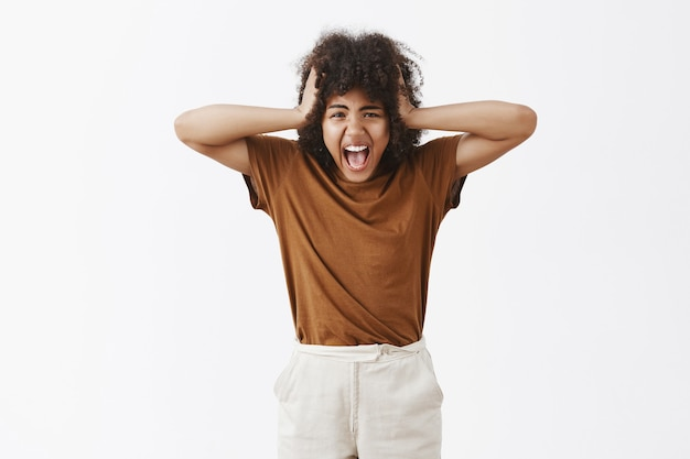 Adolescente arrabbiato arrabbiato stufo sconvolto con taglio di capelli afro che urla tenendosi per mano sulla testa essendo infelice con i genitori che litigano ogni volta che urlano da sentimenti negativi sul muro grigio, perdendo la testa