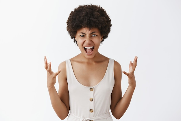 Distressed and pissed woman being under pressure, yelling and squeezing hands from anger, grimacing and frowning having argument