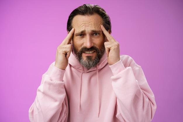 Проблемный под давлением интенсивно обеспокоенный зрелый кавказский мужчина с бородой, седыми волосами, хмурясь, гримасничая, думает, держится за руки, храмы беспокоит, не может придумать идею плана, имеет кризис, фиолетовый фон.