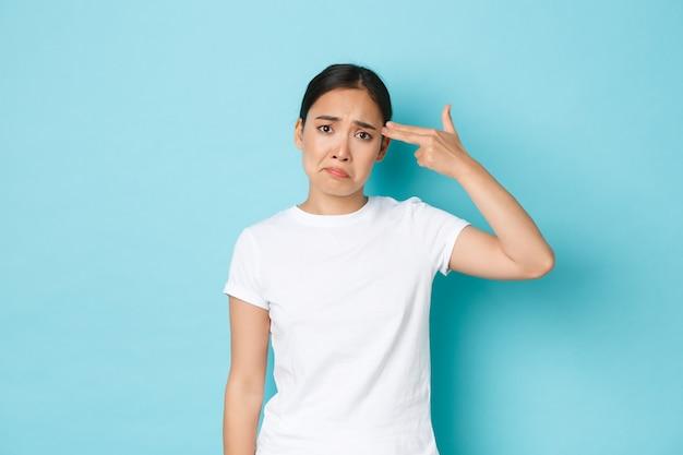 白いtシャツの苦しめられた悲しいアジアの女の子は不平を言っている、疲れているか落ち込んでいる、頭の近くでショットガンのジェスチャーをし、顔をゆがめる不安、青い壁に悩まされて立っている