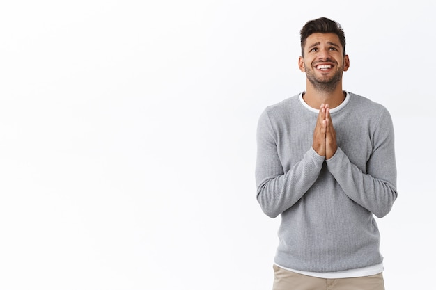 Distressed sad and nervous handsome man with beard in grey sweater, shaking hands in supplication, white wall