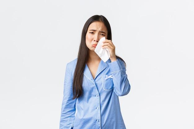 파란 잠옷을 입은 괴로워하는 어리석은 아시아 소녀는 기분이 좋지 않은 상태로 침대에 누워 있고, 티슈로 눈물을 닦고, 흐느끼고 우울하고, 흰색 배경에 대해 슬퍼하고 있습니다.