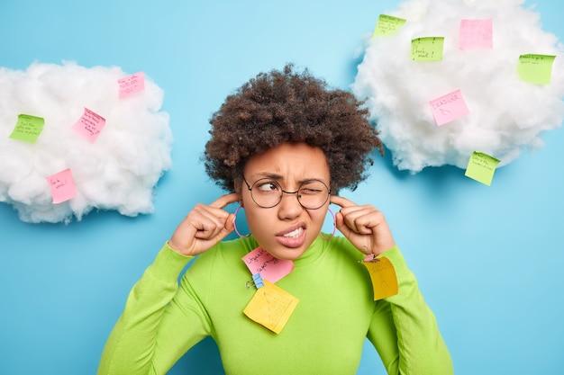 苦しめられた若いアフリカ系アメリカ人の女性は耳を塞ぎ、付箋紙に囲まれた騒音を避けます眉をひそめる顔は青い壁に隔離された丸い眼鏡の緑のタートルネックを着用します
