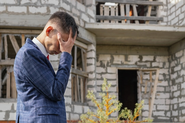 ビジネススーツを着た苦しんでいる若い男が、破壊された未完成の家の前に立っており、住宅、建設、住宅ローンの危機にお金を払うことができません