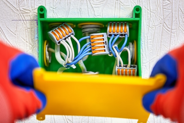 건식 벽체 수리공이 정션 박스를 닫는 아래 숨겨진 배선용 배전반