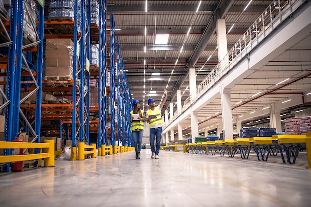 Distribution warehouse interior with workers wearing hardhats and reflective jackets walking in storage area
