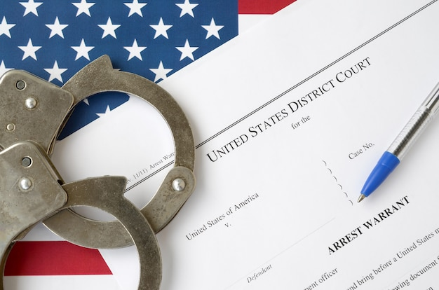 District court arrest warrant court papers with handcuffs and blue pen on united states flag. concept of permission to arrest suspect