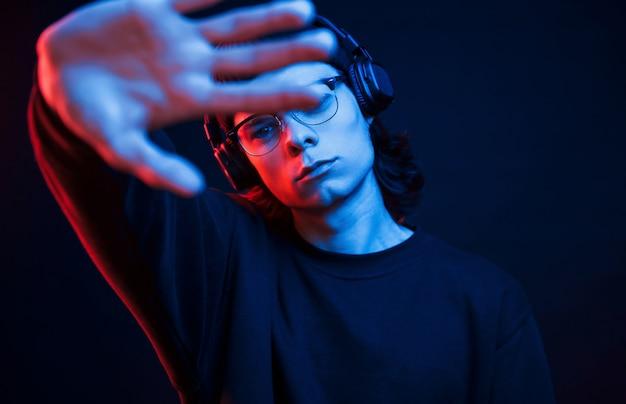 Don't disturb me. studio shot in dark studio with neon light. portrait of serious man