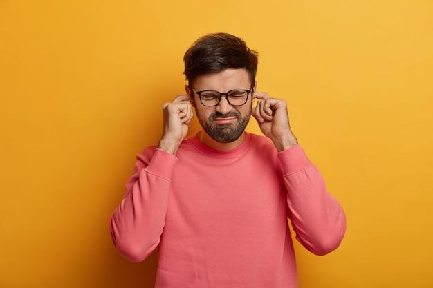 Обеспокоенный мужчина затыкает пальцами отверстия для ушей, слышит раздражающий громкий звук, шум или сирену, хмурится, небрежно одет, позирует над желтой стеной, игнорирует душераздирающий крик, исходящий из другой комнаты