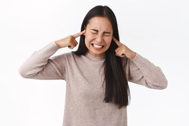 La giovane studentessa asiatica disturbata e infastidita non può studiare preparare gli esami causa la festa di lancio dei vicini rumorosi, chiudere le orecchie con le dita, fare una smorfia angosciata