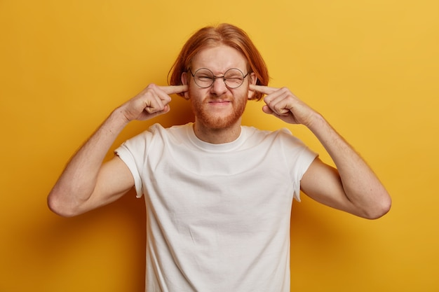 Disturbed ginger man plugs ears, ignores loud music, smirks face