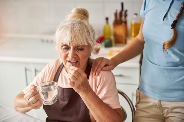 그녀의 약을 물과 함께 복용 방해 할머니