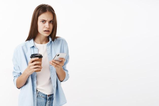 Donna impegnata alla moda sconvolta, stordita e nervosa, che tiene un bicchiere di carta con caffè e smartphone fissando scioccata e preoccupata per scoprire notizie scosse