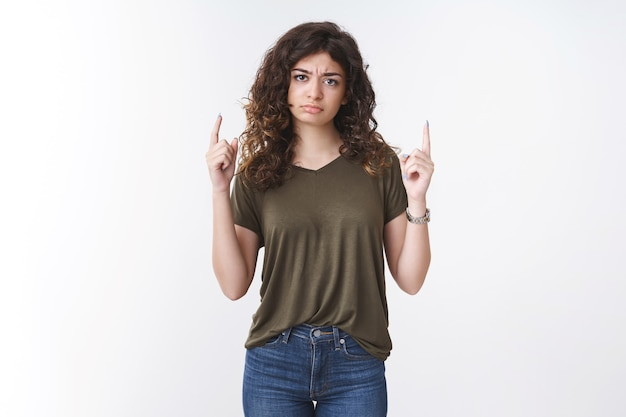 Disturbed upset let down young cute sulking armenian girlfriend pointing raised fingers up frowning pouting disappointed complaining express gloomy mood lacking interest, standing white background