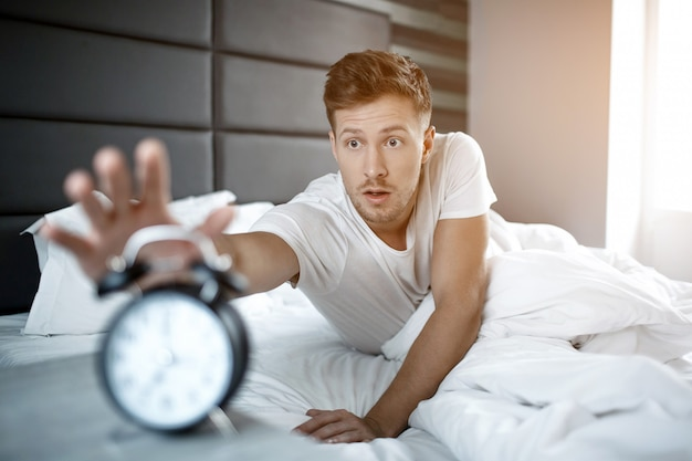 Disturbed young man lying on bed in morning. he overslept. guy reach clock with hand.