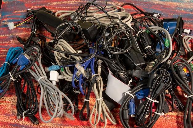 Вышедшие из употребления стопки старых компьютерных кабелей и устройств 1