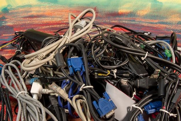 Вышедшие из употребления стопки старых компьютерных кабелей и устройств