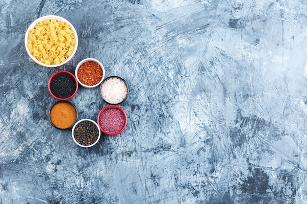 Ditalini pasta in a bowl with assorted spices top view on a grey plaster background