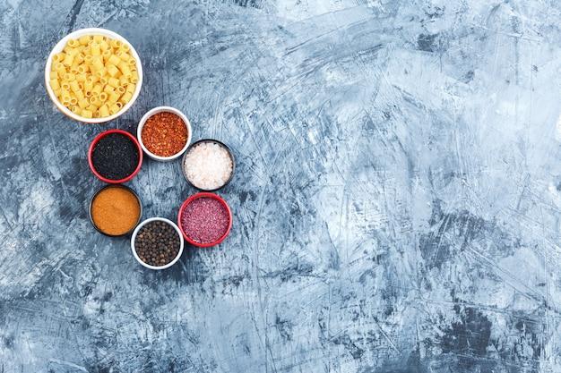 회색 석고 배경에 모듬 향신료 평면도와 그릇에 ditalini 파스타