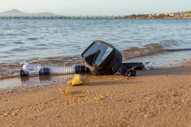 Маска для дайвинга и трубка для профессионалов на песке на фоне моря. концепция путешествий и отдыха.