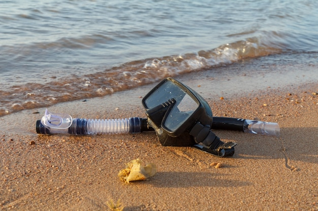 Dive mask and a snorkel for professionals on sea sand with a sea on the surface