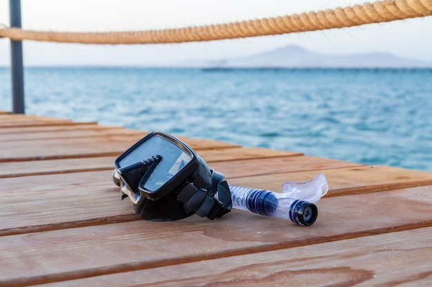 Dive mask and a snorkel for professionals on wooden pier with a sea on the surface