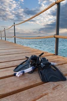 Маска для дайвинга, плавники и трубка на деревянном пирсе с морем на заднем плане. концепция путешествий и отдыха.
