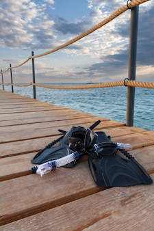 Dive mask, swimfins and a snorkel on wooden pier with a sea on the background. travel and vacation concept.
