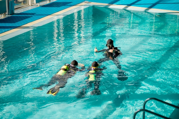 Divemaster and divers in aqualungs, dive course