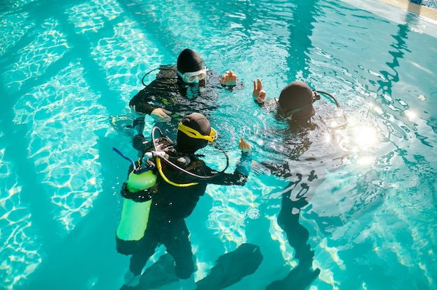 Divemaster and divers in aqualungs, diving school