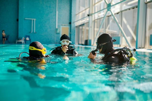 Divemaster and two divers in aqualungs, course in diving school. teaching people to swim underwater with scuba gear, indoor swimming pool interior on background, group training