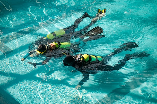 Divemaster and two divers in aqualungs, dive course in diving school. teaching people to swim underwater with scuba gear, indoor swimming pool interior on background, group training