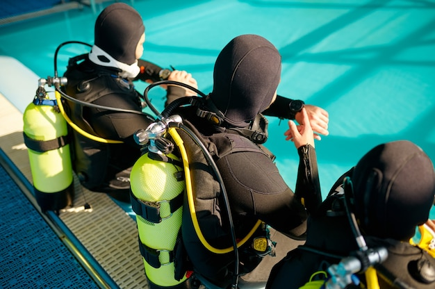 Divemaster and two divers in scuba gear preparing for the dive, diving school. teaching people to swim underwater, indoor swimming pool interior on background
