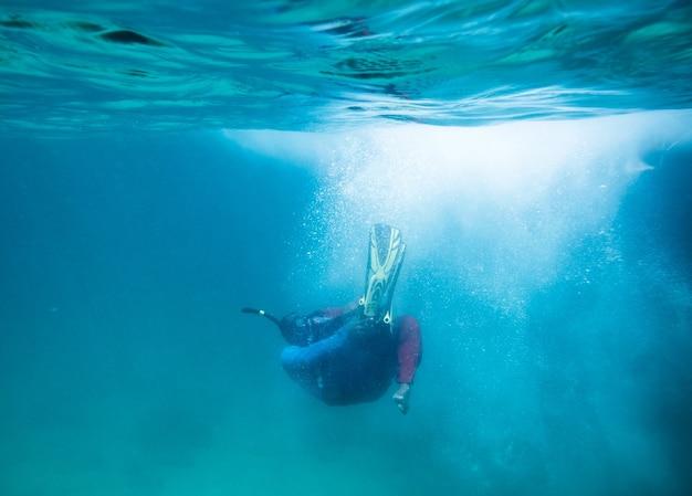 青い海に飛び込み、泡を輝かせるダイバー