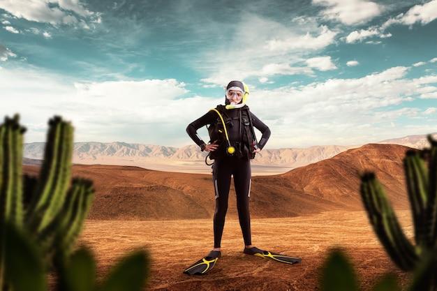 ウェットスーツのダイバーと砂漠に立っているダイビングギア。マスクとスキューバのフロッグマンが海、水中スポーツで泳ぐ