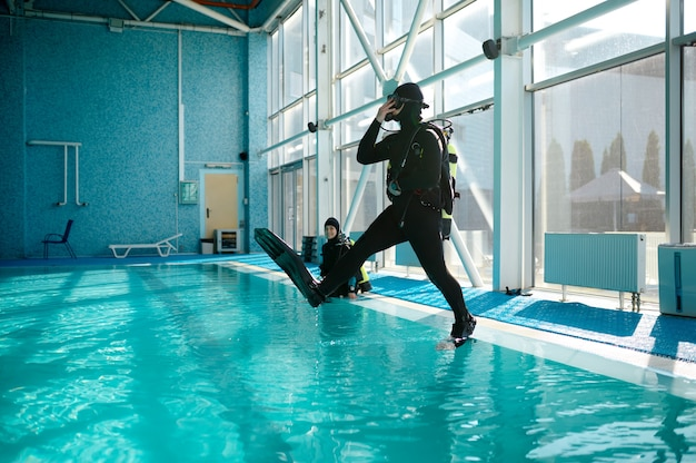 Diver in scuba gear jumps into the pool, lesson in diving school. teaching people to swim underwater, indoor swimming. men with aqualangs