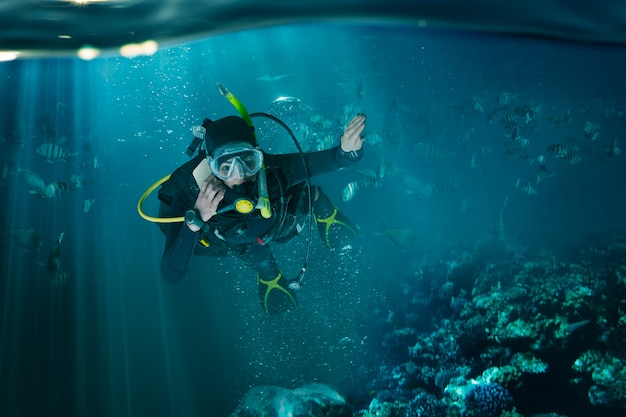 Diver in wetsuit and diving gear, underwater view