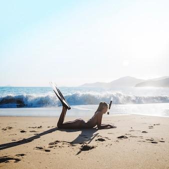 Дайвер женщина позирует на пляже