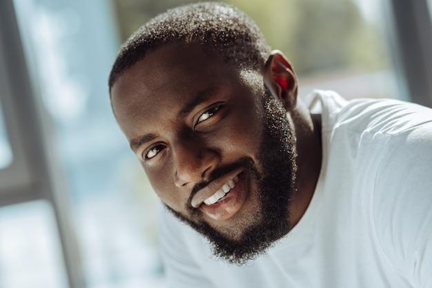 世界の多様性。喜びを表現しながらあなたを見ている笑顔のアフリカ系アメリカ人男性のクローズアップ